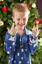 Boy Crossing Fingers In Front Of Christmas Tree Stock Image