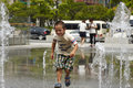 Boy crossing square hit by the fountain suddenly spraying up chines got and wet from water surprised face and funny moment Stock Photos