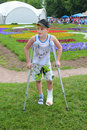 Boy on crutches in beautiful summer park Royalty Free Stock Photos