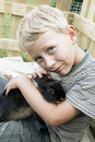 Boy cuddling up with pet rabbit blond youngster and his best friend playing outdoors and snuggling huddling a cute black dwarf Royalty Free Stock Images