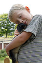 Boy cuddling up with pet rabbit blond youngster and his best friend playing outdoors and snuggling huddling a cute black dwarf Royalty Free Stock Photography
