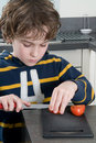 Boy cutting tomato Stock Photos