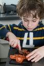 Boy cutting tomato Stock Image