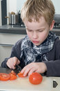 Boy cutting tomato Stock Photography