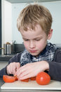Boy cutting tomato Stock Images