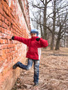 Boy dancing near the wall on background of trees Stock Image