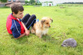 Boy dog and decorative hedgehog the teenager his sitting on the grass looking at the garden Stock Photo