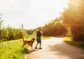 Boy and dog play together on countryside road at summer evening