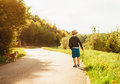 Boy and dog walk on contryside road at the evening summertime Royalty Free Stock Photo