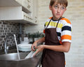 Boy doing the dishes Royalty Free Stock Photography
