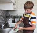 Boy doing the dishes Royalty Free Stock Images
