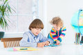 Boy doing homework and his sister watching him young school toddler in a white room next to a window Royalty Free Stock Photo