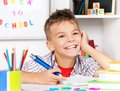 Boy doing homework young sitting at desk in the classroom at the table Stock Images
