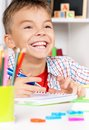 Boy doing homework young smiling sitting at desk in the classroom at the table Royalty Free Stock Photos