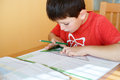 Boy doing school homework from geometry mathematics in workbook Royalty Free Stock Photos