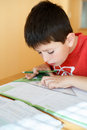Boy doing school homework from mathematics geometry in workbook Stock Photography