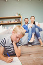 Boy drawing on book while parents looking at him from sofa in living room Stock Photos