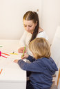 Boy drawing with colorful crayons little mother at home Royalty Free Stock Images