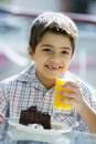 Boy drinking orange juice in cafe Stock Image