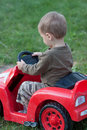 Boy driving toy car toddler his electric red on the lawn Royalty Free Stock Photo