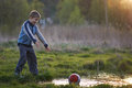 Boy dropped the ball in a puddle and shouts grass Royalty Free Stock Photo