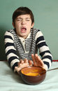 Boy eat pumpkin soup with expression of disgust Royalty Free Stock Photo