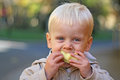Boy eating an apple the is chewing core Stock Photos