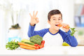 Boy eating carrot and gesturing happiness seated at table vegetables with hand home Royalty Free Stock Photo