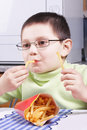 Boy eating fried potato Stock Photography