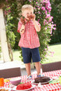 Boy Eating Jelly And Cake At Outdoor Tea Party Royalty Free Stock Photo