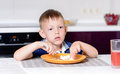 Boy Eating Last Bite of Food at Kitchen Table Royalty Free Stock Photo