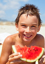 Boy eating melon on a beach Royalty Free Stock Image