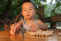 Boy eating peanuts chinese sit on bamboo chair Stock Images