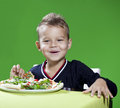Boy eating pizza the little in a pizzeria eats a to it it is cheerful also it laughs Stock Photography