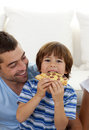 Boy eating pizza in living-room with his father Stock Photography