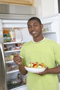 Boy Eating Salad By Open Refrigerator Royalty Free Stock Image