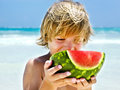 Boy eating a slice of watermelon on the beach Stock Photos