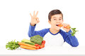 Boy eating vegetables and gesturing happiness seated at table with hand isolated on white background Royalty Free Stock Photography