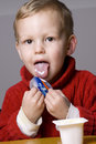 Boy eating yogurt Royalty Free Stock Image