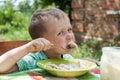 Boy eats breakfast outdoors Stock Photo