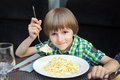 Boy eats pasta with salmon in a cafe Royalty Free Stock Photos