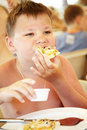 Boy eats a pizza in summer cafe on a beach Stock Photos
