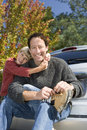 Boy embracing father beside car man sitting on bumper tying shoelace smiling portrait men Stock Photography