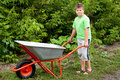 Boy with the empty wheelbarrow Stock Photo