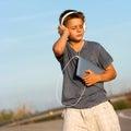 Boy enjoying music on tablet outdoors. Stock Image
