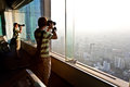Boy enjoying view across bangkok enjoys skyline and takes pictures Stock Photo