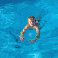 Boy enjoys swimming in the pool young Stock Photos
