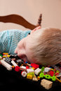 Boy falls asleep tired little in bed while playing with colorful lego pieces home background Royalty Free Stock Image
