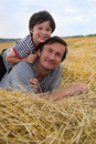 The boy and father on hay Royalty Free Stock Photography