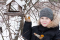 Boy feeds the birds in feeder in winter Royalty Free Stock Photo